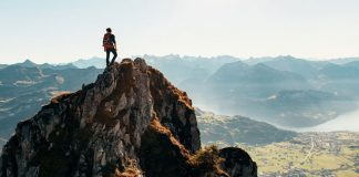 man on top of mountain after hike