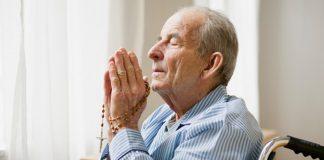 elderly man praying with rosary