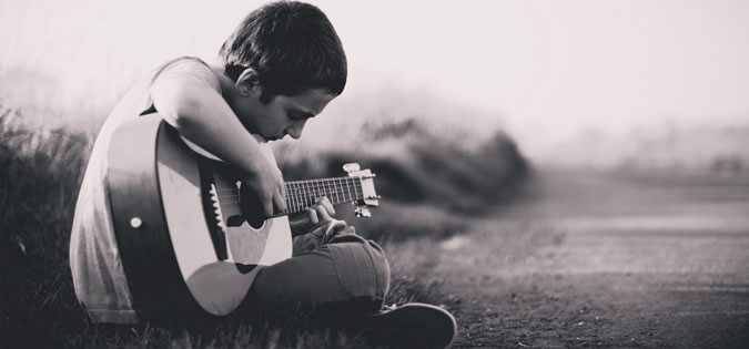 young man learning to play guitar
