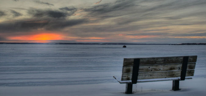 empty bench in winter at sunrise
