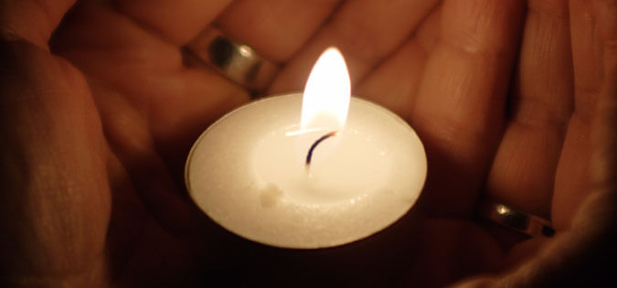 candle held in cupped hands
