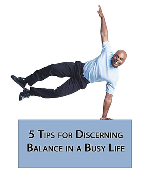 man balancing on sign - 5 Tips for Discerning Balance in a Busy Life