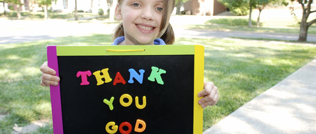 "girl holding sign reading ""Thank you, God"""