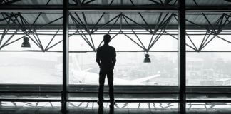 man staring out airport windows