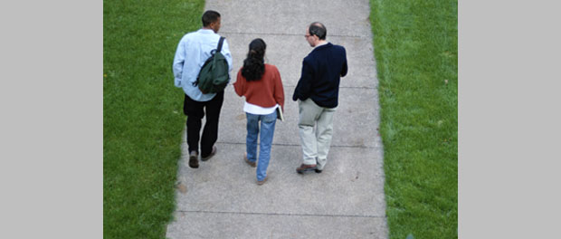 college students walking with professor