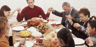 family praying around holiday table