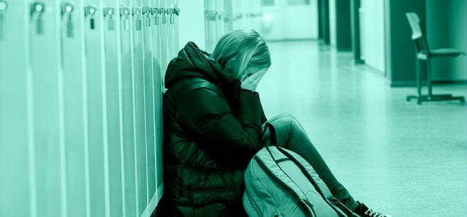 girl sitting alone in school hallway