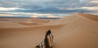 woman sitting in the desert