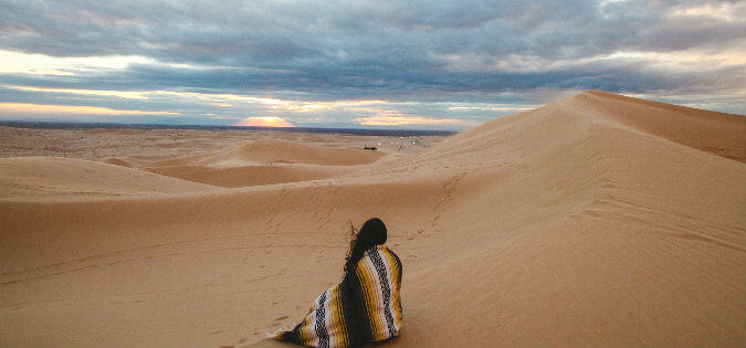 woman sitting in the desert