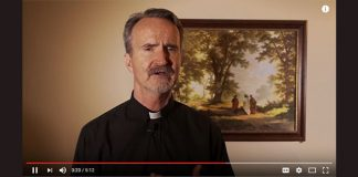 Michael Sparough, SJ, in front of Emmaus painting