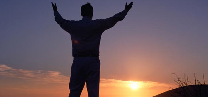 man with arms raised in praise