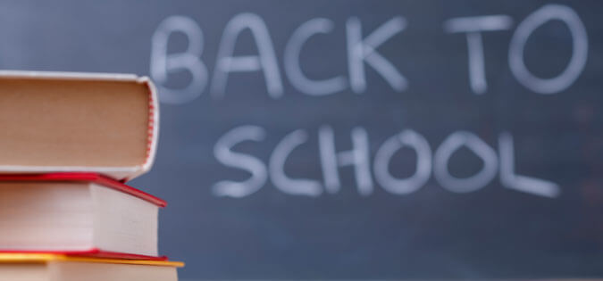 """Back to school"" written on chalkboard with books in foreground"