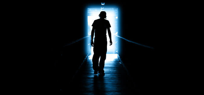 man walking through darkness to light