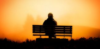 man on bench at winter sunset