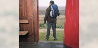 man standing in doorway ready for trip or hike