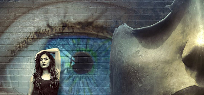 young woman standing in front of wall with eye painted on it