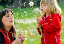 woman and young girl blowing dandelion seeds