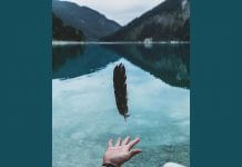 person letting go of feather - photo by Paul Gilmore on Unsplash