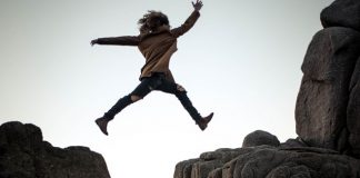 person shows courage by leaping over mountains