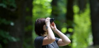 woman using binoculars - photo by Kayla Farmer on Unsplash