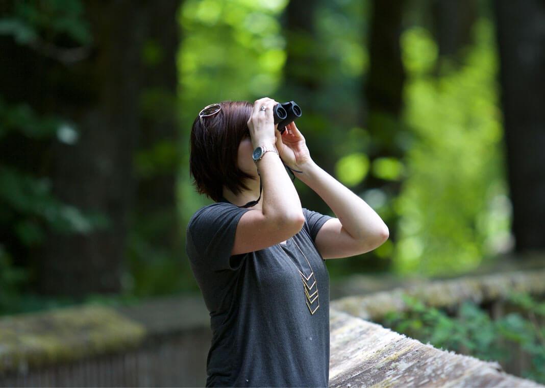 woman using binoculars - photo by Kayla Farmer on Unsplash