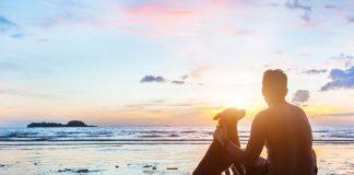 man and dog on beach in reflective scene