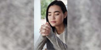 woman praying near window