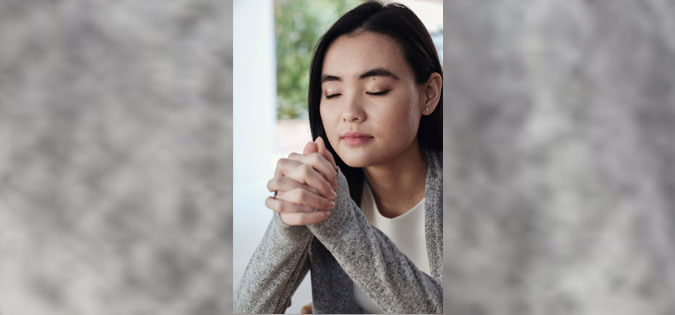 woman praying near window
