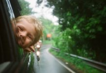 child with head out car window - photo by Anton Luzhkovsky on Unsplash
