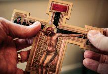 holding crucifix - photo by James Coleman on Unsplash
