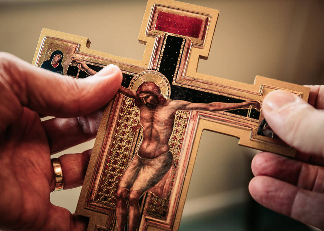 holding crucifix - photo by James Coleman on Unsplash