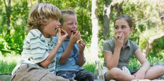 children eating outside as friends