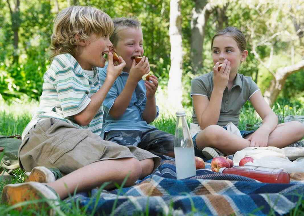 children eating outside as friends