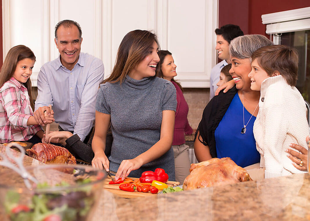 family in kitchen preparing Thanksgiving meal