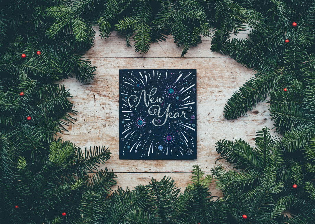 Happy New Year sign surrounded by evergreen branches - photo by Annie Spratt on Unsplash