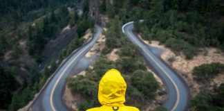 person in yellow jacket sitting at winding road overlook - photo by Justin Luebke on Unsplash