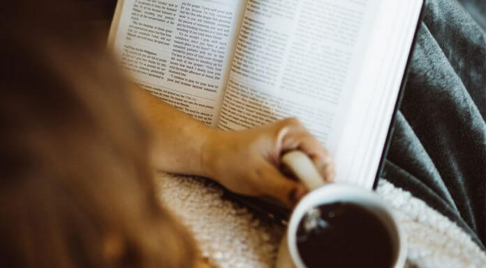 woman praying with Bible while drinking coffee
