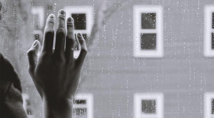 hand on rainy window - photo by Kristina Tripkovic on Unsplash
