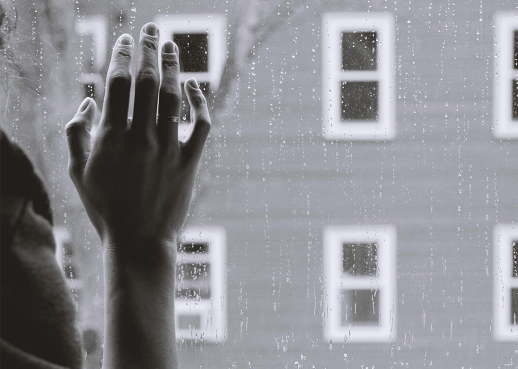hand on rainy window - photo by Kristina Tripkovic on Unsplash