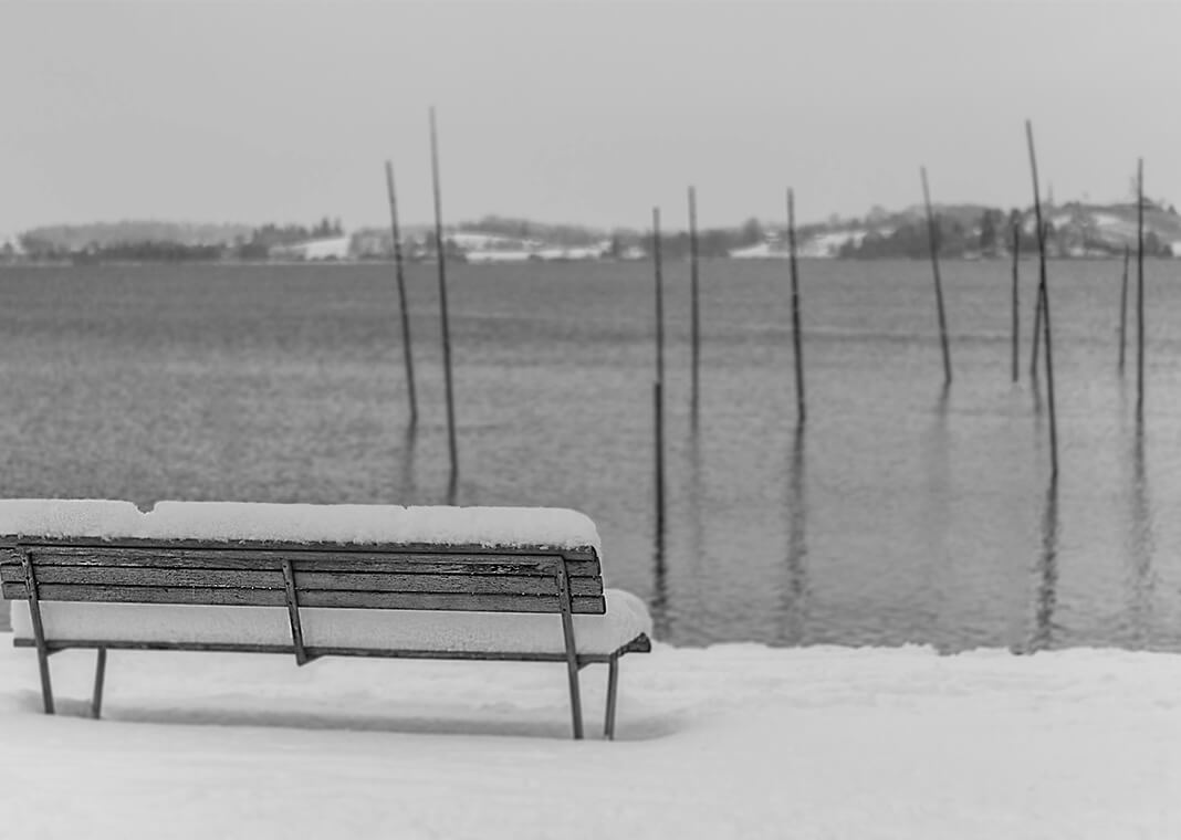 desolate winter scene of bench at water's edge - photo by Jan Huber on Unsplash