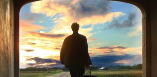 man leaving with suitcase to walk into sunrise over path - photo by Mantas Hesthaven on Unsplash
