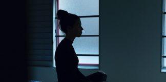 woman sitting on bed in darkness - photo by Ben Blennerhassett on Unsplash