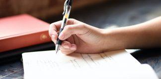 woman writing - photo by Hannah Olinger on Unsplash