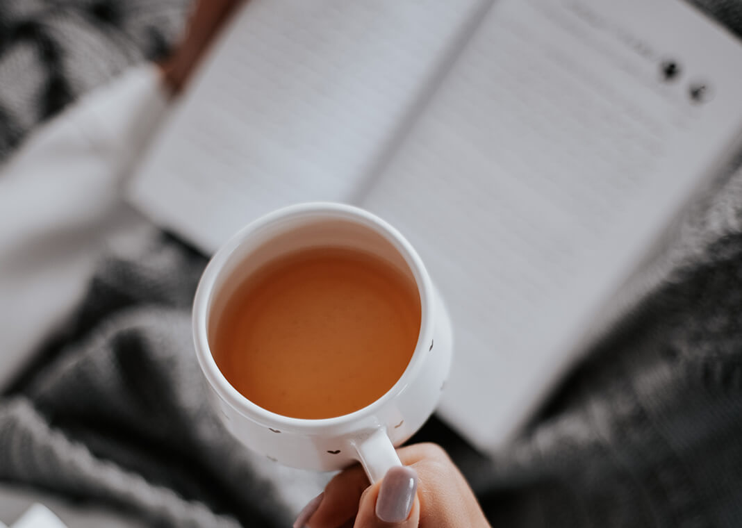 close-up of woman's teacup as she reads - photo by Farzad Mohamadi on Unsplash