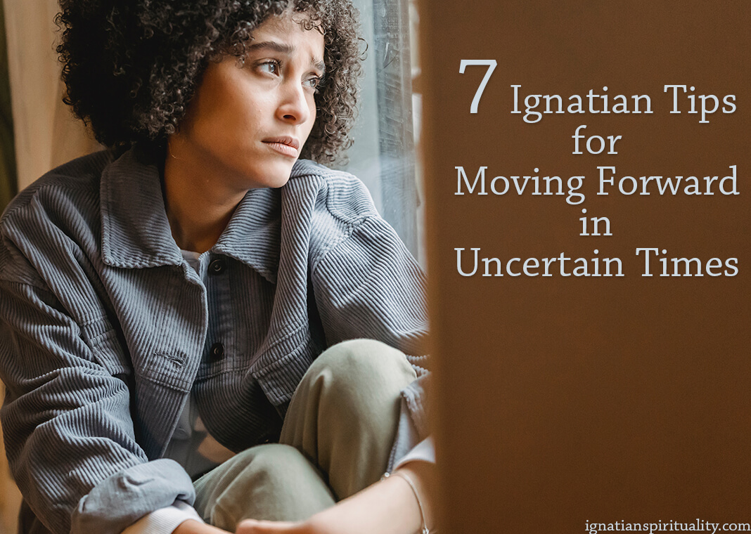 woman looking uncertainly out window - photo by Liza Summer from Pexels - text: 7 Ignatian Tips for Moving Forward in Uncertain Times